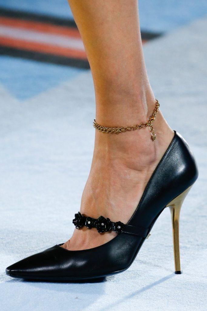 1342ee351e2 Το χρυσό τακούνι και το ιδιαίτερο λουράκι με τα λουλουδάκια κάνουν  ιδιαίτερα ρομαντική αυτήν την μάλλον κλασική μαύρη γόβα του Versace. Ένα  παπούτσι από τη ...